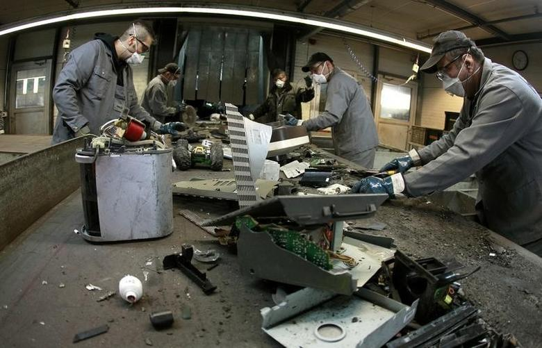 Workers sort electronic scrap on a conveyor belt at a plant of Swiss recycling company Immark AG in the town of Regensdorf near Zurich April 8, 2013.  REUTERS/Arnd Wiegmann