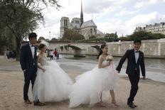 Two Chinese couples walk to attend their a pre-wedding photoshoots in front of the Notre-Dame Cathedral in Paris, France, August 28, 2015. REUTERS/Philippe Wojazer