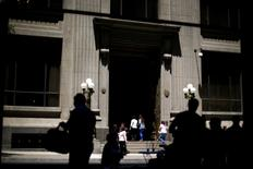 Peatones pasan junto a la entrada principal del Banco Central de Chile, en Santiago, 7 de noviembre de 2014. El Banco Central de Chile rebajó su estimación de crecimiento de la economía para este año y elevó con fuerza su cálculo de la inflación por los efectos de la depreciación del peso, lo que podría dar paso a una eventual alza de la tasa de interés clave hacia fin de año. REUTERS/Ivan Alvarado