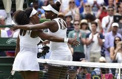 Serena Williams of the U.S.A. embraces Venus Williams of the U.S.A. after winning their match at the Wimbledon Tennis Championships in London, July 6, 2015.                  REUTERS/Toby Melville