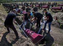 """Рабочие опускают гроб в могилу на похоронах 57 неопознанных украинских военных в поселке Кушугум 7 августа 2015 года. Число погибших за полтора года войны между правительственными войсками и пророссийскими сепаратистами на востоке Украины достигло почти 8.000, сообщила во вторник ООН, назвав оценку """"консервативной"""". REUTERS/Gleb Garanich"""
