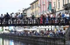 People walk along the Naviglio Gran Canal in Milan, August 29, 2015.REUTERS/Flavio Lo Scalzo