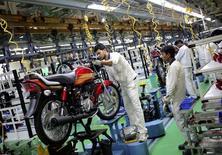 Empleados trabajan en la línea de ensamblaje de Hero Motocorp, durante un tour para los medios en la planta en Neemrana, India, 20 de octubre de 2014. Hero MotoCorp, uno de los mayores fabricantes de motocicletas del mundo, inauguró el martes una planta ensambladora en Colombia en la que invirtió 70 millones de dólares, como parte de un plan de expansión internacional que apunta a conquistar el mercado de América Latina. REUTERS/Anindito Mukherjee