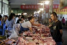 Los fabricantes chinos recortaron precios en agosto a su ritmo más acelerado en seis años, después de que los precios de las materias primas cayeran y la demanda se enfriara, lo que sugiere unos riesgos persistentes de deflación sobre la economía y aumenta las expectativas de nuevas medidas de estímulo. En la imagen, una vendedora trata de alcanzar una pieza de cerdo en un mercado de Pekín, el  12 de agosto de 2015. REUTERS/Jason Lee