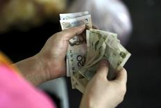 Un cliente sostiene billetes de yuan chino, en un mercado en Pekín, 12 de agosto de 2015. Los bancos chinos ofrecieron en agosto 809.600 millones de yuanes en nuevos préstamos netos en moneda local, incumpliendo las expectativas de los analistas y por debajo de los préstamos del mes anterior. REUTERS/Jason Lee