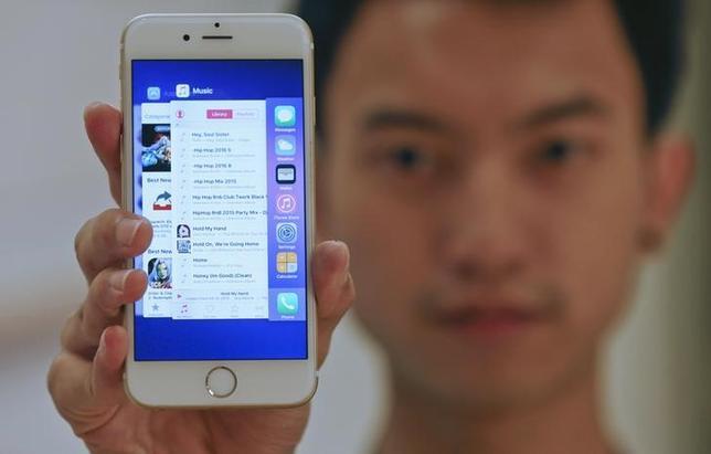 9月18日、米アップルのモバイル基本ソフト「iOS9」のアップデート時に不具合が生じた問題で、専門家からは製品に不満を持つ層の増加がリスクになるとの懸念が出ている。写真はiOS9にアップデートしたiPhoneを持つ男性。バンコクで撮影(2015年 ロイター/CHAIWAT SUBPRASOM)