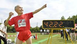 105-year-old Japanese Hidekichi Miyazaki poses like Jamaica's Usain Bolt in front of an electric board showing his 100-metre record time of 42.22 seconds at an athletic field in Kyoto, Japan, in this photo taken by Kyodo September 23, 2015.  REUTERS/Kyodo