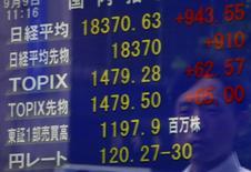 Un peatón se refleja en una pantalla que muestra el índice Nikkei y la tasa cambiaria entre el dólar estadounidense y el yen, afuera de una correduría en Tokio, Japón, 9 de septiembre de 2015. Las bolsas de Asia caían el viernes y el dólar se fortalecía después de que la presidenta de la Reserva Federal, Janet Yellen, sugirió que el banco central de Estados Unidos aún está en camino de subir las tasas de interés este año. REUTERS/Yuya Shino