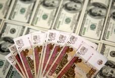 Рублевые и долларовые купюры в Сараево 9 марта 2015 года. Рубль за счет текущего роста нефтяных котировок сократил до минимума утренние потери в ответ на вчерашнее существенное падение нефти и окончание сентябрьского налогового периода. REUTERS/Dado Ruvic