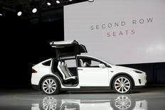 A Tesla Motors Model X electric sports-utility vehicle opens its falcon wing doors on stage during a presentation in Fremont, California September 29, 2015.  REUTERS/Stephen Lam
