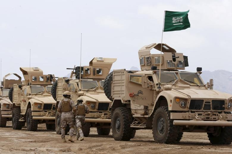 Saudi troops walk past armoured personnel carriers at their base in Yemen's southern port city of Aden September 28, 2015. REUTERS/Faisal Al Nasser