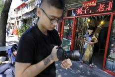 Chinese artist ROBBBB prepares to take pictures of people along a street for his artworks in Beijing's Gulou area, September 25, 2015. REUTERS/Jason Lee