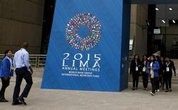 Unas personas en la entrada del evento organizado por el FMI y el Banco Mundial en Lima, oct 5, 2015. El Fondo Monetario Internacional recortó el martes sus previsiones de crecimiento mundial por segunda vez este año, citando la debilidad de los precios de las materias primas y una desaceleración en China, y advirtió que se necesitan políticas encaminadas a aumentar la demanda.   REUTERS/Mariana Bazo