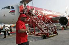 Tony Fernandes, CEO of AirAsia, walks near an AirAsia Airbus A320 at the domestic airport in Manila in this May 23, 2014 file photo.  REUTERS/Romeo Ranoco/Files