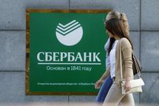 Женщины проходят мимо отделения Сбербанка в Москве 12 сентября 2014 года. Чистая прибыль крупнейшего госбанка РФ Сбербанка, рассчитанная по российским стандартам, в январе-сентябре 2015 года сократилась на 49,6 процента до 144,4 миллиарда рублей из-за роста расходов на резервы, сообщил банк в среду. REUTERS/Sergei Karpukhin