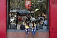Женщины у кофейни Coffee Day в Мумбаи. 25 февраля 2015 года. Индийская Coffee Day Enterprises Ltd, управляющая крупнейшей сетью кофеен в стране, готовится провести самое большое IPO в Индии за последние три года, ожидая, что инвесторы оценят компанию в 67,5 миллиарда рупий ($1,04 миллиарда). REUTERS/Shailesh Andrade