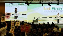 """Diretora-geral da ANP, Magda Chambriard, discursa durante leilão, enquanto manifestantes protestam contra """"fracking"""". 07/10/2015 REUTERS/Pilar Olivares"""