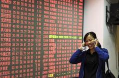 Una inversora habla en su celular mientras camina junto a un tablero electrónico que muestra la información de las acciones, en una correduría en hangzhou, China, 8 de octubre de 2015. Las acciones chinas registraron el jueves su mayor avance en dos semanas de negociación, poniéndose al día con un repunte en los mercados globales tras un receso de una semana, pero el volumen de comercio se mantuvo débil en medio de las preocupaciones de los inversores sobre el enfriamiento de la economía. REUTERS/Stringer