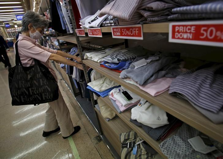 A woman wearing a mask looks at clothes at a retail store at a business district in Tokyo, September 15, 2015.  REUTERS/Yuya Shino