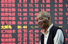 Un inversor frente a un tablero electrónico que muestra la información de las acciones, en una correduría en Hangzhou, China, 15 de octubre de 2015.  Las acciones chinas recuperaron el impulso al alza el jueves, saltando por encima de un 2 por ciento en medio de señales de que el dinero ha comenzado a fluir de nuevo hacia la renta variable, mientras que la celebración de una reunión clave del Partido Comunista este mes ha aumentado las expectativas de nuevas medidas de estímulo. REUTERS/China Daily