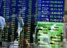 Peatones reflejados en un tablero electrónico que muestra la información de las acciones, en una correduría en Tokio, Japón, 29 de septiembre de 2015. Las bolsas de Asia operaban el lunes cerca de máximos en dos meses luego de que una serie de datos de China revelaron que, aunque su economía se está ralentizando, no está en peligro de un aterrizaje forzoso. REUTERS/Issei Kato