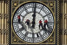 Cleaners abseil down one of the faces of Big Ben, to clean and polish the clock face, above the Houses of Parliament, in central London in this file picture taken August 19, 2014. REUTERS/Toby Melville