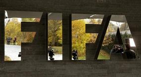 Jornalistas refletidos no logo da Fifa do lado de fora da sede da entidade, em Zurique. 20/10/2015    REUTERS/Arnd Wiegmann