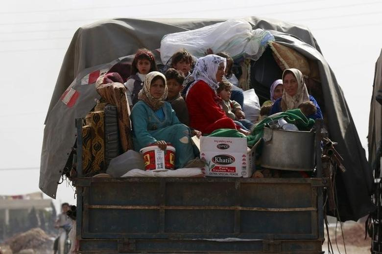 Civilians fleeing the recent fightings in their area sit at the back of a pickup truck with their belongings in the southern countryside of Aleppo, Syria October 21, 2015. REUTERS/Hosam Katan