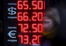 Женщина у пункта обмена валюты в Москве. 18 августа 2015 года. Рубль в плюсе на торгах среды за счет восстановления нефти с 6-недельных минимумов, из-за которых рубль тестировал утром 3-недельное дно; поддержку ему могли оказать и корпоративные продавцы валюты, проявившиеся на рынке по мере значительного роста котировок доллара в начале дня, а также закрытие спекулятивных длинных валютных позиций. REUTERS/Maxim Shemetov
