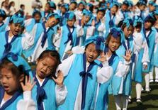 Дети в китайских традиционных костюмах во время школьной церемонии в Наньтуне. 16 сентября 2015 года. Коммунистическая партия Китая в четверг пообещала смягчить ограничения, касающиеся планирования семьи, и разрешить каждой паре иметь по двое детей. REUTERS/China Daily