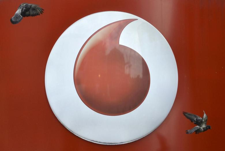 Pigeons fly past Vodafone branding outside a retail store in London November 12, 2013.  REUTERS/Toby Melville