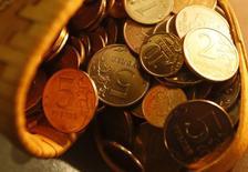 Рублевые монеты в Красноярске 12 января 2015 года. Рубль в понедельник пытался закрепиться на положительной территории, отыгрывая рост нефтяных котировок, но участники рынка сохраняли осторожность из-за рисков повышения процентной ставки по доллару уже в декабре, что играет на стороне валюты США и против сырьевых и развивающихся валют. REUTERS/Ilya Naymushin