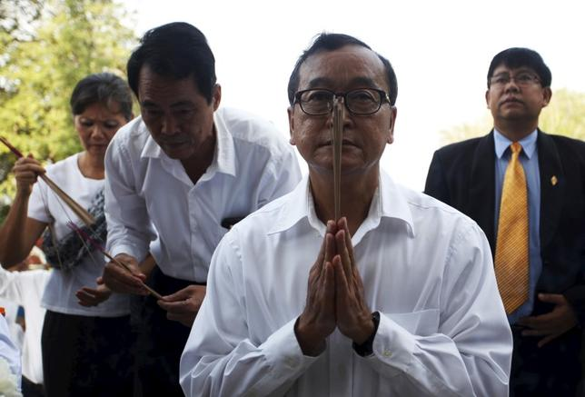 Sam Rainsy (C), President of the Cambodia National Rescue Party (CNRP), prays in front of the skulls and bones of more than 8,000 victims of the Khmer Rouge regime during a Buddhist ceremony at Choeung Ek, a ''Killing Fields'' site located on the outskirts of Phnom Penh, April 17, 2015.  REUTERS/Samrang Pring