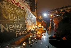 Flowers and candles are placed near the scene of a shooting the day after a series of deadly attacks in Paris, France, November 14, 2015. REUTERS/Yves Herman