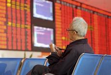 An investor writes on papers as he sits in front of an electronic board showing stock information at a brokerage house in Fuyang, Anhui province, China, October 8, 2015. REUTERS/Stringer