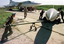 Военнослужащие буксируют крылатую ракету в направлении бомбардировщика Ту-22 в Уссурийске 17 сентября 1999 года. Россия, которая во вторник совершает большое число ударов с воздуха по целям в Сирии, предварительно уведомила Вашингтон, что будет применять крылатые ракеты морского базирования и бомбардировщики дальнего действия в ходе операции, сообщил чиновник Пентагона. STR New / Reuters