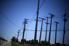 Unos postes eléctricos junto a una carretera en Santiago, nov 7, 2014. Una corte chilena rechazó el martes la demanda de dos administradoras de fondos de pensiones (AFP) que buscaba frenar la reorganización del grupo energético Enersis y sus filiales, una operación que será votada el próximo mes por sus accionistas.     REUTERS/Ivan Alvarado