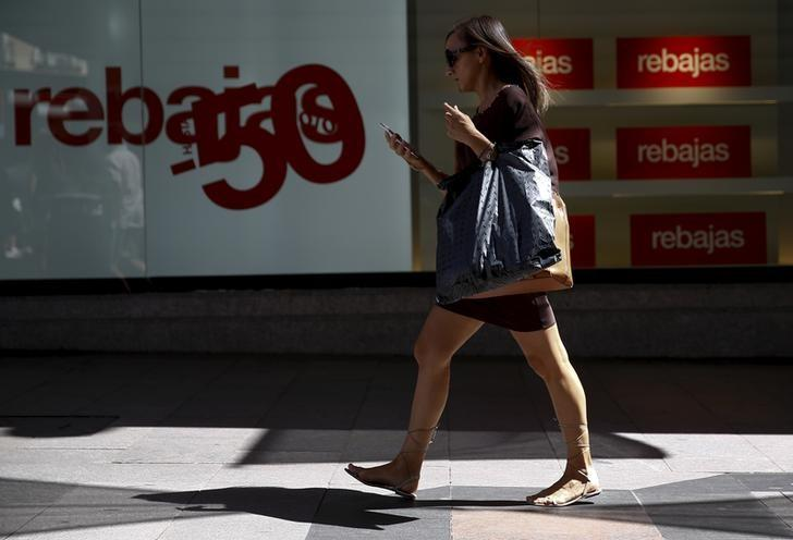 A woman carries a shopping bag as she checks her mobile phone in central Madrid, Spain, August 26, 2015. REUTERS/Sergio Perez