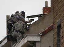 Belgian special forces police climb high on an apartment block during a raid, in search of suspects linked to the deadly attacks in Paris, in the Brussels suburb of Molenbeek, November 16. 2015.    REUTERS/Yves Herman