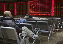 Un inversor sentado frente a un tablero electrónico que muestra información bursátil, en Pekín, China, 18 de noviembre de 2015. Las acciones chinas cayeron casi un 1 por ciento el miércoles luego de que un repunte en los valores ligados al sector inmobiliario, impulsado por unos datos positivos de precios de casas, fue contrarrestado por declives en otros sectores. REUTERS/Li Sanxian