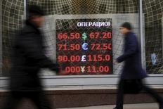 Люди проходят мимо экрана пункта обмена валюты в Москве. 13 ноября 2015 года. Рубль торговался на пятничной сессии в узких диапазонах, реагируя в основном на внутридневные колебания нефти и изменения пары евро/доллар на форексе при низкой активности участников рынка после нескольких дней роста российской валюты. REUTERS/Maxim Zmeyev