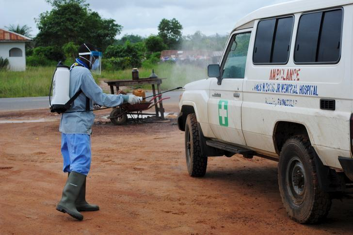 A health worker sprays disinfectant on an ambulance in Nedowein, Liberia, July 15, 2015. REUTERS/James Giahyue