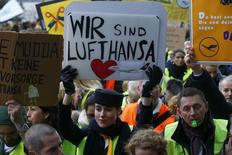 A Lufthansa employee holds up a placard reading 'we are Lufthansa' during a strike by cabin crew union (UFO) at Frankfurt airport, Germany, November 13, 2015.  REUTERS/Ralph Orlowski