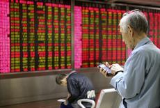 Un inversor mira su celular frente a un tablero electrónico que muestra la información de las acciones, en una correduría en Pekín, China, 16 de noviembre de 2015. El índice bursátil ChiNext, dominado por los valores de baja capitalización, saltó casi un 3 por ciento el miércoles a un máximo en cuatro meses, lo que impulsó al mercado más amplio en China, que fue lastrado inicialmente por los sectores cíclicos. REUTERS/Li Sanxian