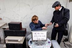 A man returns a cell phone to a customer after downloading music onto it at a street stand in Shanghai January 22, 2009. REUTERS/Nir Elias