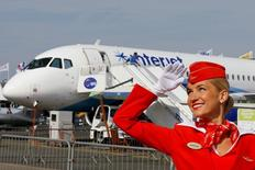 A cabin crew member of Russian carrier Aeroflot poses in front of a Sukhoi Superjet 100 airplane during a photo session at the 51st Paris Air Show at Le Bourget airport near Paris, June 16, 2015. REUTERS/Pascal Rossignol