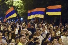 Протестующие держат в руках флаги Армении на митинге против роста цен на электричество в Ереване 1 июля 2015 года. Граждане Армении проголосовали за ограничение полномочий президента и усиление роли главы правительства, показали опубликованные в понедельник данные плебисцита, который критики назвали ширмой для укрепления правящей верхушки. REUTERS/Hayk Baghdasaryan