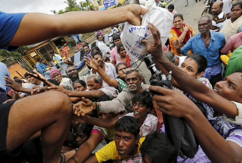 Flood-affected people raise their hands to receive free food being distributed by Indian Navy personnel in Chennai, India, December 5, 2015. REUTERS/Anindito Mukherjee
