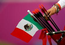 Mexico's Aida Roman takes an arrow from her quiver, in which a Mexican national flag can be seen, during the women's archery individual round of 8 eliminations at the London 2012 Olympic Games at the Lord's Cricket Ground August 2, 2012.  REUTERS/Suhaib Salem