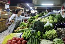 Una clienta compra vegetales en un mercado en Qingdao, China, 14 de octubre de 2015. La inflación a los consumidores de China se aceleró levemente en noviembre, pero seguía bien por debajo del objetivo del 3 por ciento fijado por el Gobierno para 2015, provocando el temor a que la segunda mayor economía del mundo sea arrastrada a una trampa deflacionaria al estilo de Japón. REUTERS/Stringer